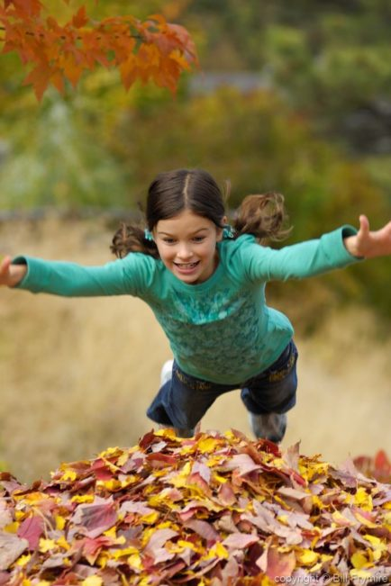 Girl jumping in the leaves